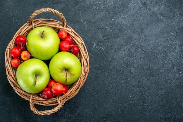 Vista superior da cesta com frutas, maçãs e cerejas no fundo escuro frutas composição da baga frescura planta