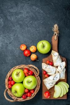 Vista superior da cesta com frutas, maçãs verdes e cerejas doces em uma mesa cinza-escuro.