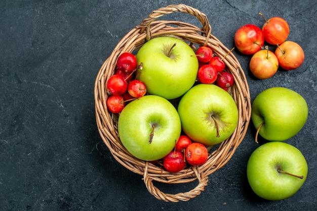 Vista superior da cesta com frutas, maçãs verdes e cerejas doces em uma superfície cinza-escuro composição de frutas árvore de frescor suave