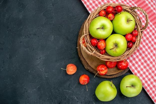 Vista superior da cesta com frutas, maçãs verdes e cerejas doces na superfície cinza escuro árvore de frescor de composição de frutas baga