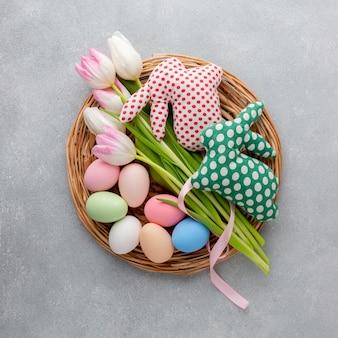 Vista superior da cesta com ovos de páscoa e tulipas
