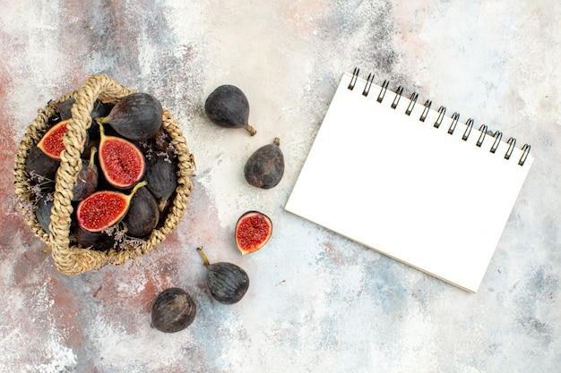 Vista superior da cesta de figos com um caderno em fundo cinza