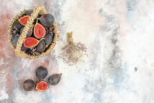 Vista superior da cesta de figos, figos, ramo de flores secas em fundo cinza