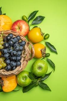 Vista superior da cesta de frutas com cachos de uvas caquis maçãs com folhas