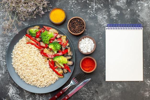 Vista superior da cevada com saborosos vegetais cozidos e temperos na mesa cinza