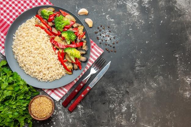 Vista superior da cevada pérola com saborosos vegetais cozidos e talheres na mesa cinza