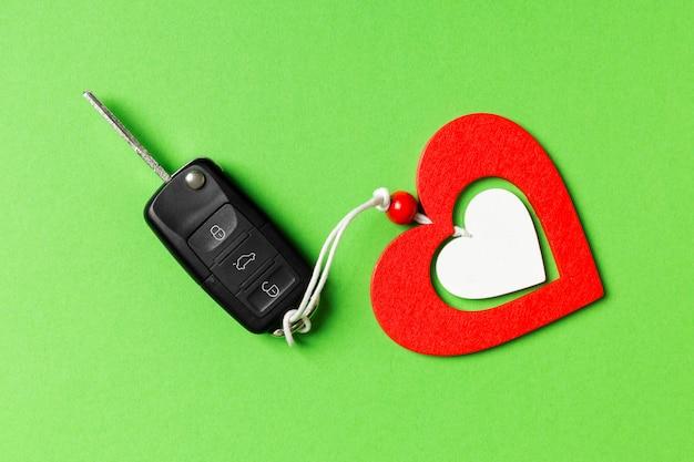 Vista superior da chave do carro e coração de madeira na mesa.