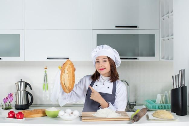 Vista superior da chef feminina de uniforme em pé atrás da mesa com alimentos da tábua de corte segurando e apontando o pão na cozinha branca
