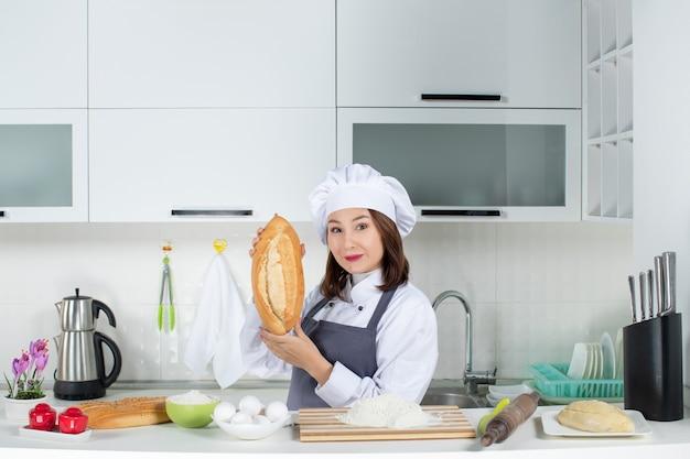 Vista superior da chef feminina de uniforme em pé atrás da mesa com uma tábua e alimentos mostrando pão na cozinha branca