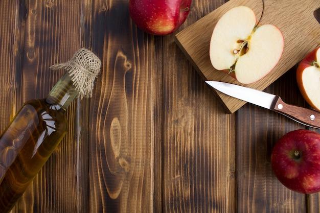 Vista superior da cidra de vinagre de maçã na garrafa de vidro na superfície de madeira