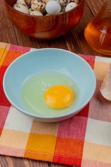 Vista superior da clara de ovos e gema em uma tigela azul em uma toalha xadrez com vinagre de maçã em um fundo de madeira