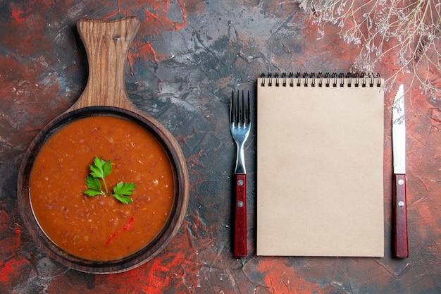 Vista superior da clássica sopa de tomate em uma tábua de corte marrom e um caderno em fundo de cor mista