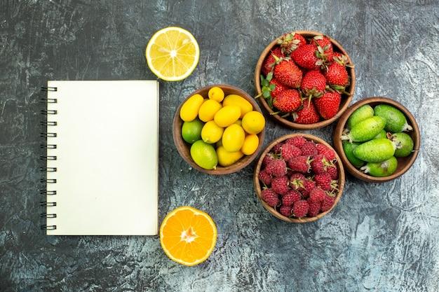 Vista superior da coleção de frutas frescas em baldes e caderno espiral em fundo escuro