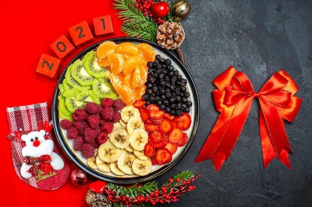 Vista superior da coleção de frutas frescas no prato de jantar acessórios de decoração ramos de abeto e números em um guardanapo vermelho e fita vermelha