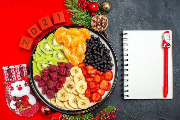 Vista superior da coleção de frutas frescas no prato de jantar acessórios de decoração ramos de abeto e números meia de natal em um guardanapo vermelho próximo caderno com caneta em um fundo preto