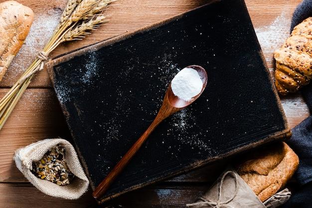 Vista superior da colher com farinha na mesa de madeira