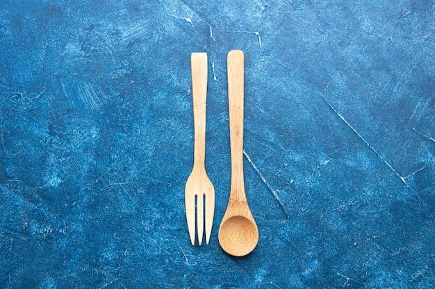Vista superior da colher de garfo de madeira na mesa azul com espaço livre