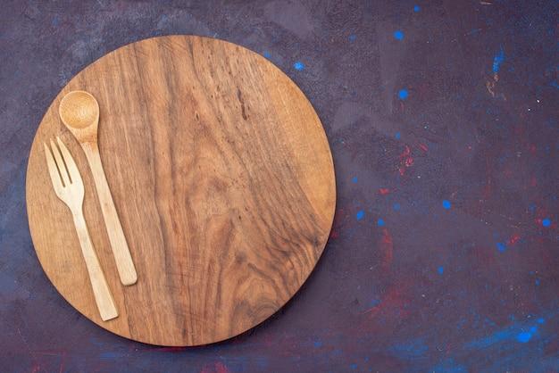 Vista superior da colher de garfo de madeira na mesa de talheres de madeira de superfície escura