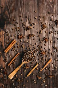 Vista superior da colher de madeira vintage, grãos de café, canela e anis estrelado em fundo de madeira.