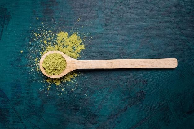 Vista superior da colher de pau de chá verde matcha em pó no fundo esmeralda.