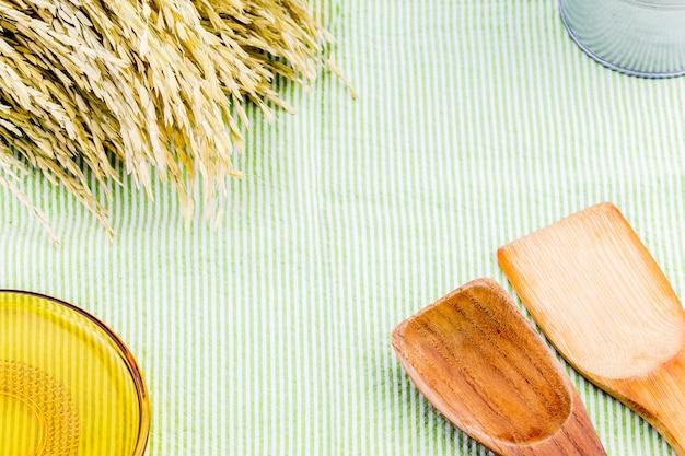 Vista superior da colher de pau, placa de vidro amarela e orelha de arroz na mesa com toalha de mesa verde