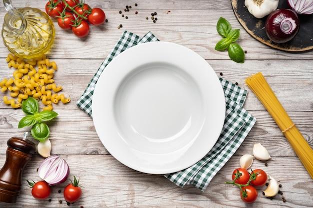 Vista superior da comida cozinhando uma mesa de madeira com vegetais, ervas, especiarias, massas e um prato branco vazio