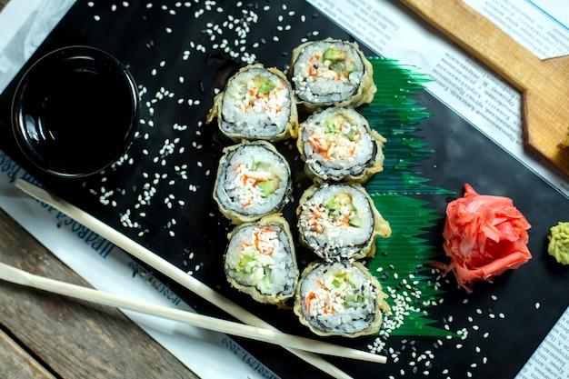 Vista superior da comida japonesa tradicional tempura sushi maki servido com gengibre e molho de soja em um quadro negro