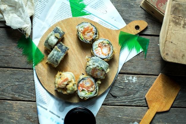 Vista superior da comida japonesa tradicional tempura sushi maki servido com gengibre e molho de soja em uma placa de madeira