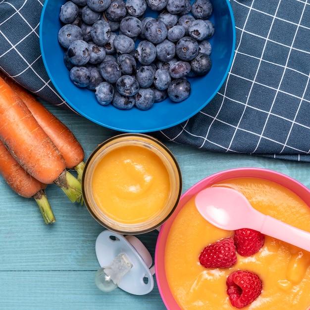 Vista superior da comida para bebê com mirtilos e cenouras