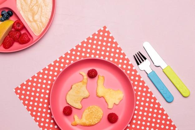 Vista superior da comida para bebê no prato com framboesas