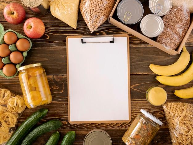 Vista superior da comida para doação com caixa e bloco de notas
