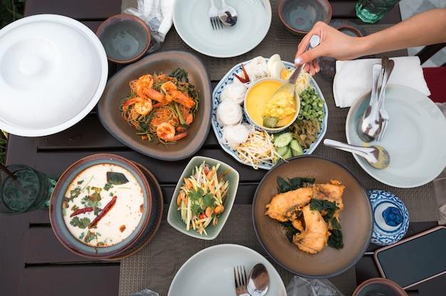 Vista superior da comida tailandesa com caranguejo salgado, macarrão de arroz, robalo frito, manga picante fatiada, canja de galinha cremosa, salada de aletria e louças na mesa do restaurante