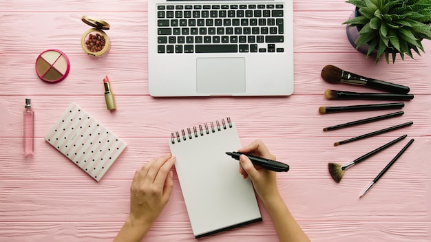 Vista superior da composição criativa decorada com cosméticos, ferramentas de maquiagem, produtos de maquiagem e mãos de mulher, escrevendo no caderno na superfície de cor. beleza, moda e conceito de compras.