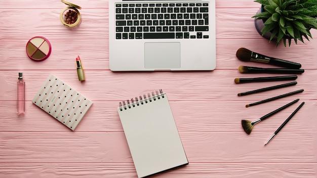 Vista superior da composição criativa decorada com cosméticos, ferramentas de maquiagem, produtos de maquiagem, notebook e laptop na superfície de cor. beleza, moda e conceito de compras.