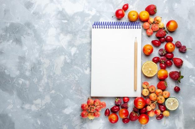 Vista superior da composição da fruta com bloco de notas na mesa de luz vitamina madura fresca e madura
