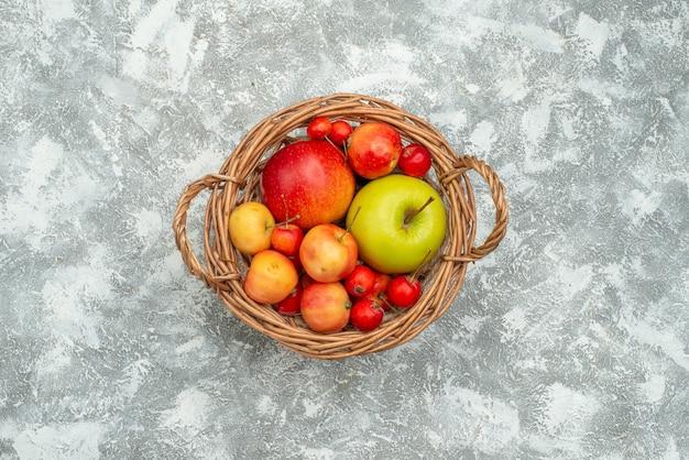 Vista superior da composição da fruta com diferentes frutas frescas dentro da cesta no espaço em branco