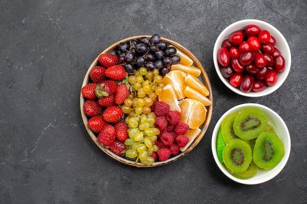 Vista superior da composição da fruta com diferentes frutas frescas em um espaço cinza escuro