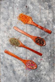 Vista superior da composição de chá seco fresco com sabor de flor em espaço rústico cinza