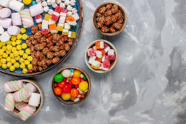 Vista superior da composição de doces de diferentes cores com marshmallow na parede branca.