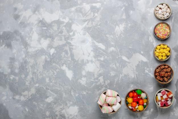 Vista superior da composição de doces, doces de cores diferentes com marshmallow dentro de potes na mesa branca.
