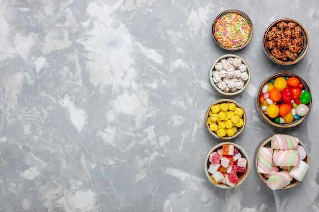 Vista superior da composição de doces, doces de cores diferentes com marshmallow dentro de potes na parede branca.