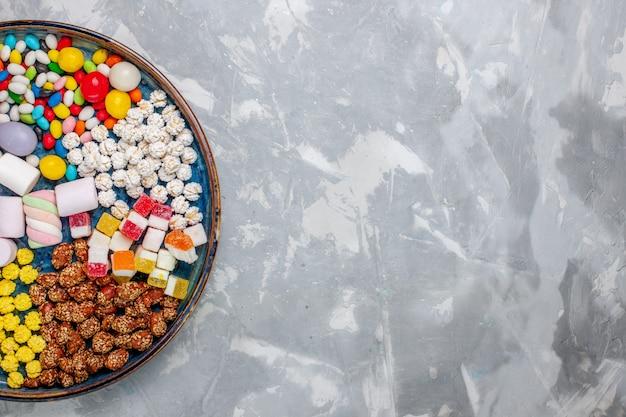 Vista superior da composição de doces, doces de cores diferentes com marshmallow na mesa branca.