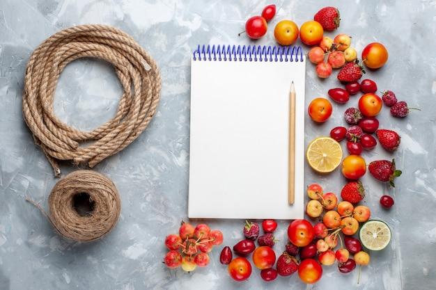 Vista superior da composição de frutas com bloco de notas e cordas na mesa de luz frutas frescas e maduras vitaminas maduras