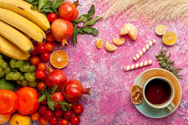 Vista superior da composição de frutas frescas com uma xícara de chá na superfície rosa claro