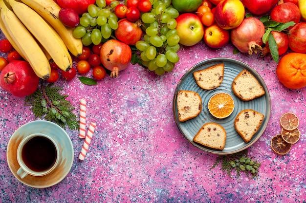 Vista superior da composição de frutas frescas frutas coloridas com bolos fatiados e uma xícara de chá na superfície rosa