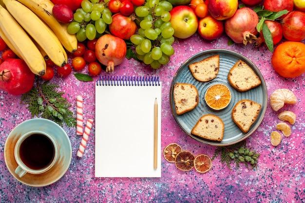 Vista superior da composição de frutas frescas frutas coloridas com bolos fatiados e xícara de chá na mesa rosa