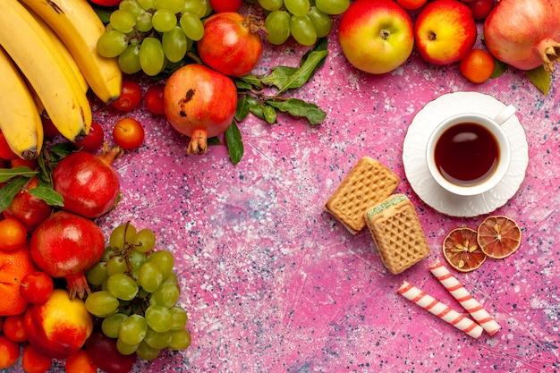 Vista superior da composição de frutas frescas frutas coloridas com chá e waffles na superfície rosa