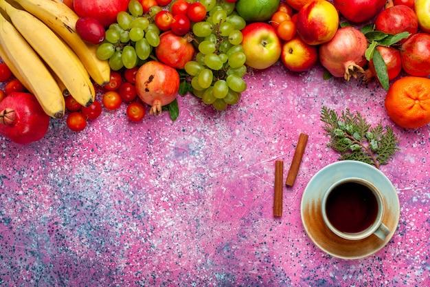 Vista superior da composição de frutas frescas frutas coloridas com chá na superfície rosa claro