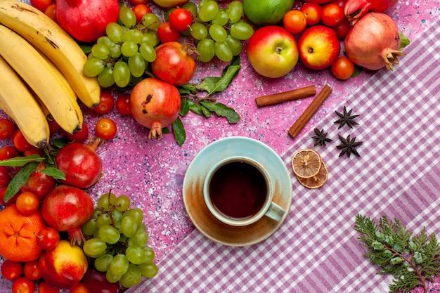Vista superior da composição de frutas frescas frutas coloridas com uma xícara de chá na superfície rosa claro