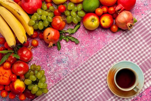 Vista superior da composição de frutas frescas frutas coloridas com uma xícara de chá na superfície rosa